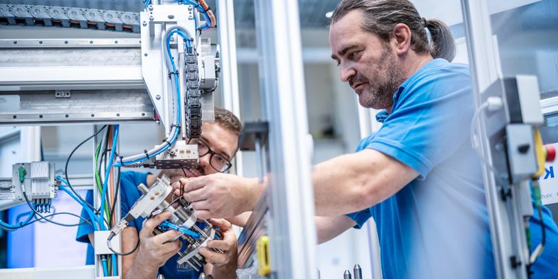 Zwei Männer bearbeiten Komponenten einer Maschine.