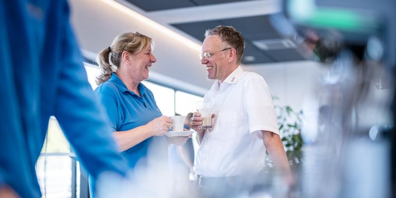Zwei Mitarbeiter trinken Kaffee und unterhalten sich.